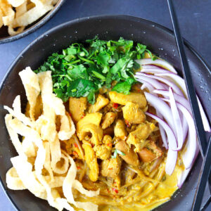 Close up top view of bowl with Khao Soi Gai with fried wonton wrapper strips, chopped coriander and mint leaves, and sliced red onion. Crossed chopsticks on top of side of the bowl, and lime wedges and crispy wonton wrapper strips in bowls behind.