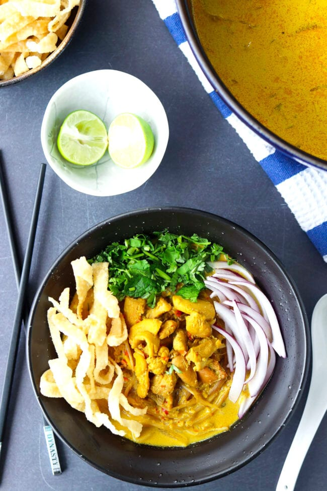 Top view of bowl with Khao Soi Gai topped with fried wonton wrapper strips, chopped coriander and mint leaves, and sliced red onion. Crossed chopsticks on and spoon on either side of bowl. Dutch oven with soup, and lime wedges and fried wonton wrapper strips in bowls behind.