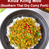 "Top view of minced pork stir-fry on rice in black bowl. Text overlay ""Khua Kling Moo (Southern Thai Dry Curry Pork)""."