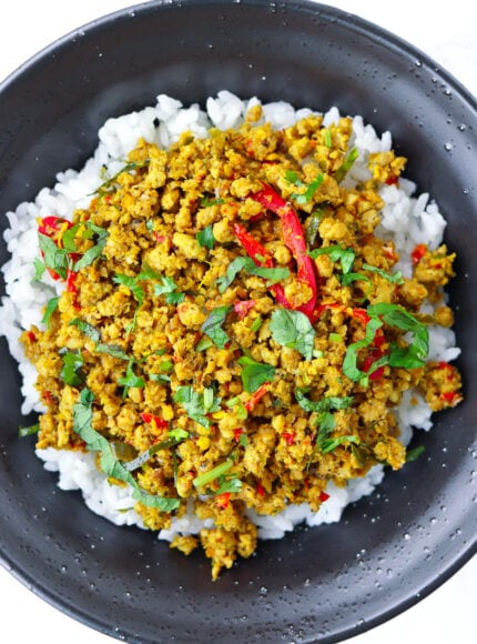 Close up top view of Khua Kling Moo on rice garnished with coriander and mint leaves in a black bowl.