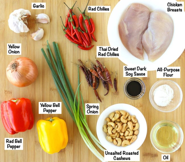 Labeled ingredients for Thai Cashew Chicken on a wooden board.