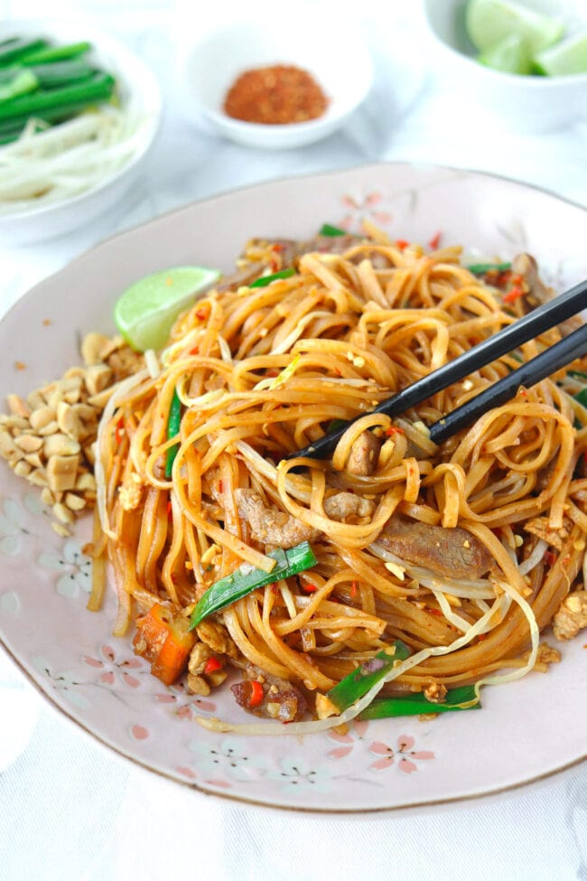 "Stir-fried noodles with black chopsticks on pink plate. Text overlay ""Spicy Pork Pad Thai""."