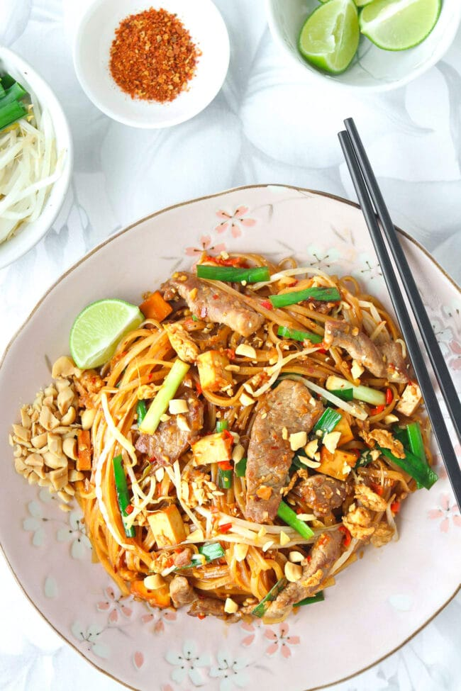 Top view of plate with Spicy Pork Pad Thai and crushed peanuts, a lime wedge, and chopsticks. Small bowls with lime wedges, bean sprouts and Chinese chives, and ground hot pepper behind.
