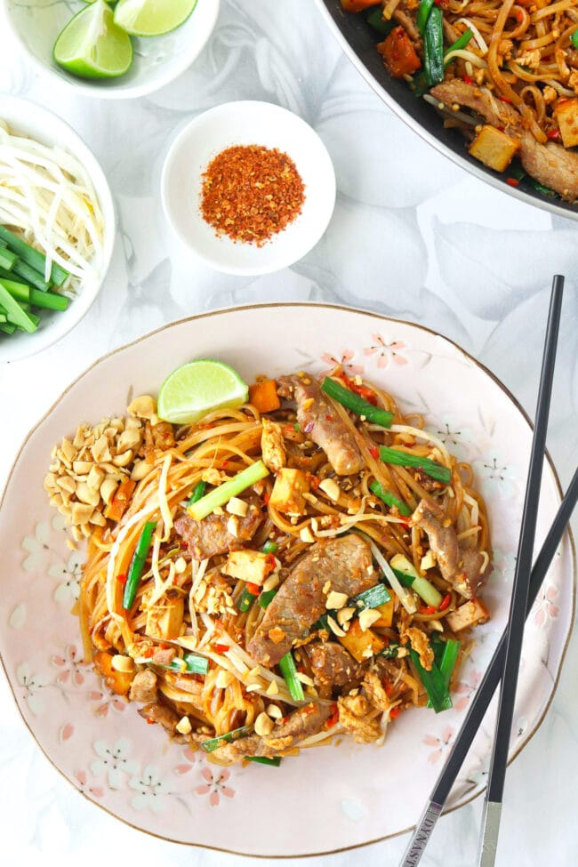 Top view of stir-fried thin rice noodles with seared pork slices on a plate with crushed peanuts, chopsticks, and a lime wedge. Wok with noodles, and small bowls with lime wedges, bean sprouts and Chinese chives, and ground hot pepper behind.