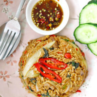 """Top view of fried rice, cucumber slices, fish sauce with chopped chilies in small dish, and spoon and fork on a plate. Text overlay """"Spicy Thai Basil Chicken Fried Rice""""."""