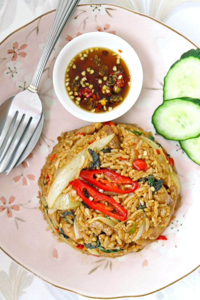 Close up top view of fried rice, cucumber slices, fish sauce with chopped chilies, and spoon and fork on a plate.