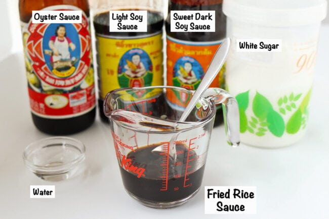 Labeled sauce ingredients for Spicy Thai Basil Chicken Fried Rice, and fried rice sauce in a measuring cup with spoon.