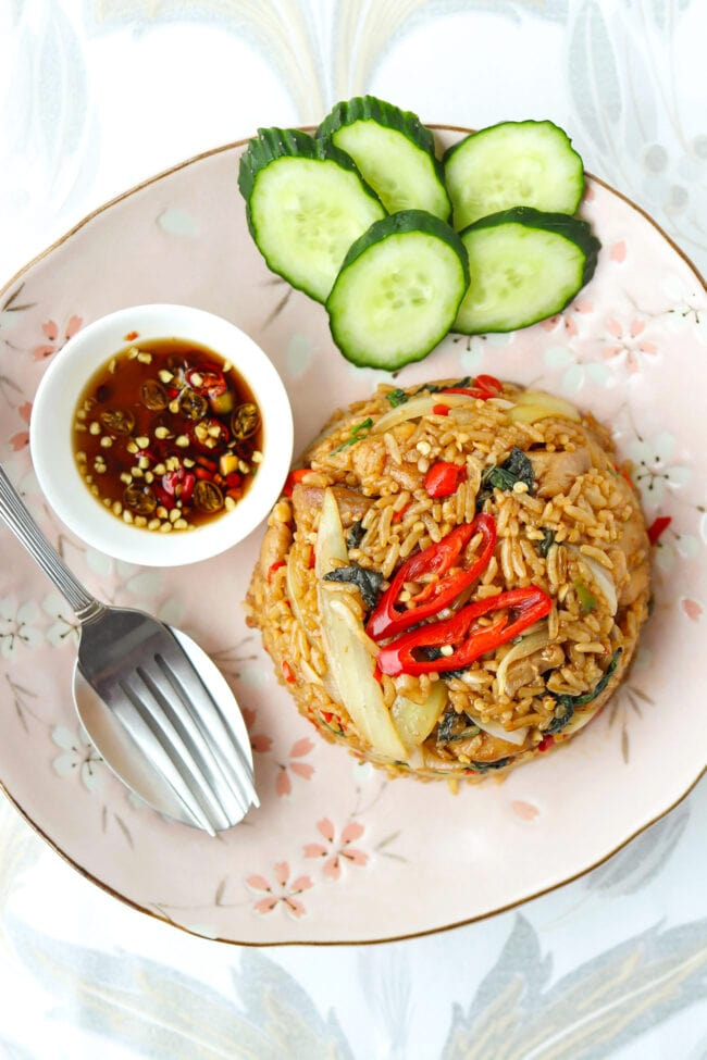 Top view of chicken fried rice on a plate with cucumber slices, fork and spoon, and small dish with chopped chilies in fish sauce.