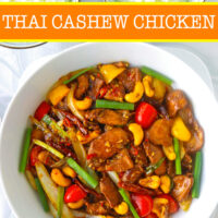 "Top view of stir-fry chicken dish with bell peppers and cashews in a serving bowl, and two bowls with rice. Text overlay ""Thai Cashew Chicken""."