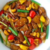 Top view of stir-fry chicken dish with bell peppers and cashews in a round serving bowl.