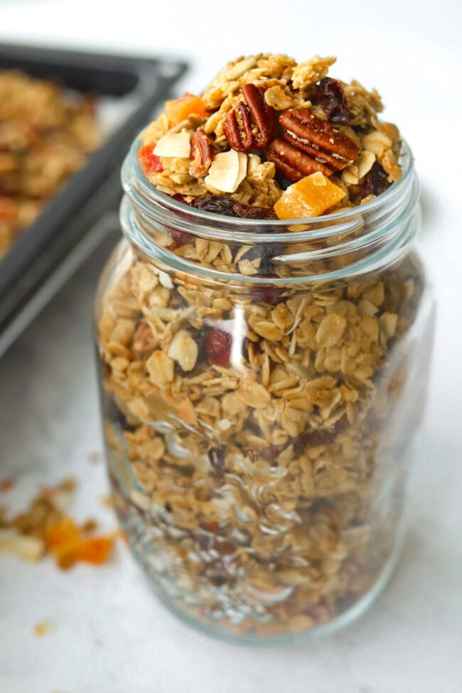 Front view of overfilled mason jar with granola, and scattered clusters around jar.