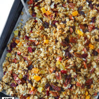 "Granola with pecans, coconut flakes, and dried fruit and spoon on parchment paper lined baking tray. Text overlay ""Tropical Pecan Coconut Granola"", ""Easy"", ""Customizable"", and ""Refined Sugar Free""."