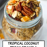 "Close up top front view of granola in mason jar, and baking tray with granola in the back. Text overlay ""Tropical Pecan Coconut Granola"", and ""Easy - Customizable - Refined Sugar Free""."