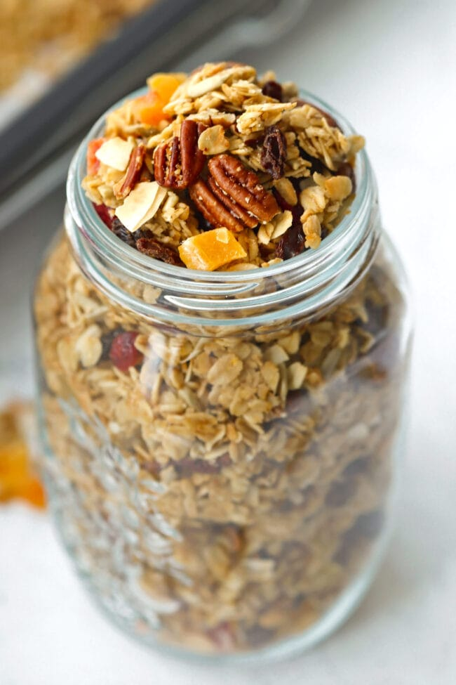 Tilted front view of granola in mason jar. Baking tray with granola in the back.