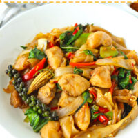 "Stir-fried rice noodles with chicken and basil dish on a plate. Text overlay ""Pad Kee Mao Gai"", ""Thai Drunken Noodles with Chicken"", and ""thatspicychick.com""."