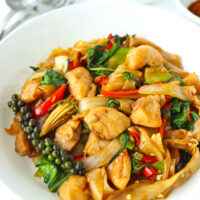 "Front view of plate with stir-fried rice noodles with chicken dish. Text overlay ""Pad Kee Mao Gai"" and ""Thai Drunken Noodles with Chicken""."