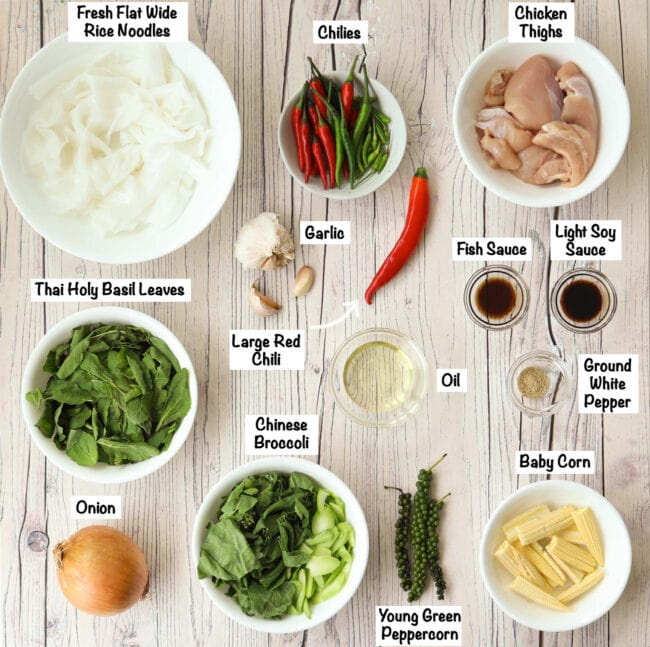 Labeled ingredients to make Pad Kee Mao Gai on wooden background.