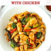 "Top view of stir-fried fresh flat wide rice noodles with chicken on a plate. Text overlay ""Pad Kee Mao Gai Thai Drunken Noodles with Chicken""."