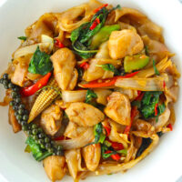 "Close up top view of stir-fried fresh flat wide rice noodles with chicken on a plate. Text overlay ""Pad Kee Mao Gai Thai Drunken Noodles with Chicken""."