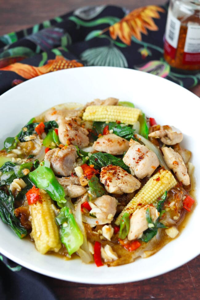 Front view of flat wide rice noodles dish with gravy, chicken, and veggies on plate.