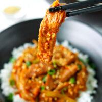 "Chopsticks holding up a pork strip above bowl with pork stir-fry and rice. Text overlay ""Spicy Korean Pork Stir-fry""."