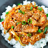 "Close-up front view of bowl with spicy pork stir-fry on rice. Text overlay ""Spicy Korean Pork Stir-fry""."