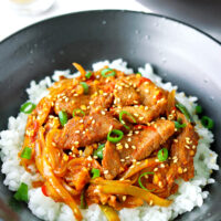 "Front view of bowl with spicy pork stir-fry on rice. Text overlay ""Spicy Korean Pork Stir-fry""."