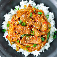 "Close-up top view of bowl with spicy pork stir-fry on rice. Text overlay ""Spicy Korean Pork Stir-fry"" and ""thatspicychick.com""."