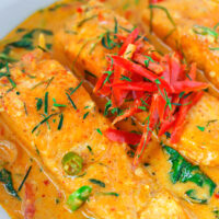 "Front close-up view of Thai salmon curry in a white round serving bowl. Text overlay ""Choo Chee Salmon Curry"" and ""thatspicychick.com""."