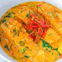 "Front view of Thai salmon curry in a white round serving bowl. Text overlay ""Choo Chee Salmon Curry"" and ""thatspicychick.com""."