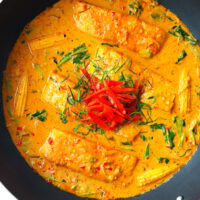 "Top view of Thai salmon thick red curry in a black. Text overlay ""Choo Chee Salmon Curry"" and ""thatspicychick.com""."