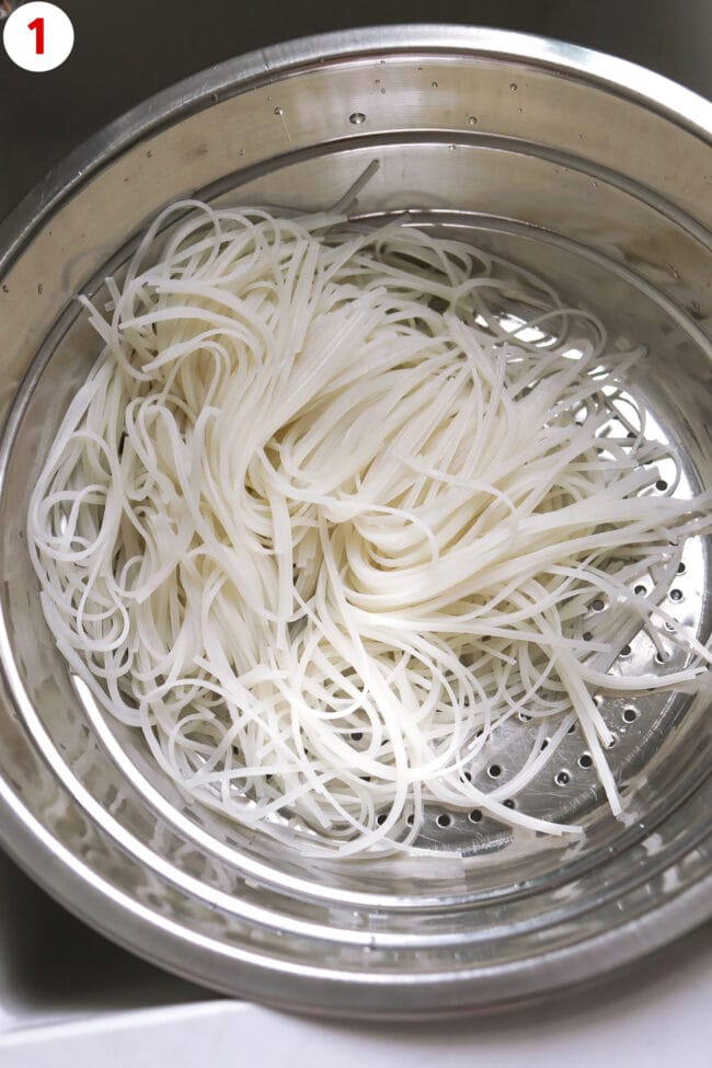 Drained rice stick noodles in colander over sink.