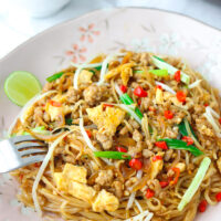 "Front view of plate with fork tucked into stir-fried noodles dish. Text overlay ""Pad Mee Korat"" and ""Pad Thai's Spicier Cousin!""."