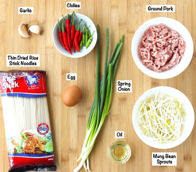 Labeled photo of stir-fry ingredients for Pad Mee Korat on wooden board.