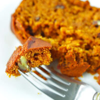 """Fork with a bite of bread on a plate with a slice behind. Text overlay """"Pumpkin Pecan Bread"""" and """"thatspicychick.com""""."""