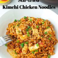 "Front view of plate with stir-fried spicy Korean noodles dish and a fork. Text overlay ""Stir-fried Kimchi Chicken Noodles"" and ""thatspicychick.com""."