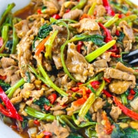 """Close up front view of bowl with lamb and veggies stir-fry. Text overlay """"Taiwanese Lamb and Water Spinach Stir-fry""""."""