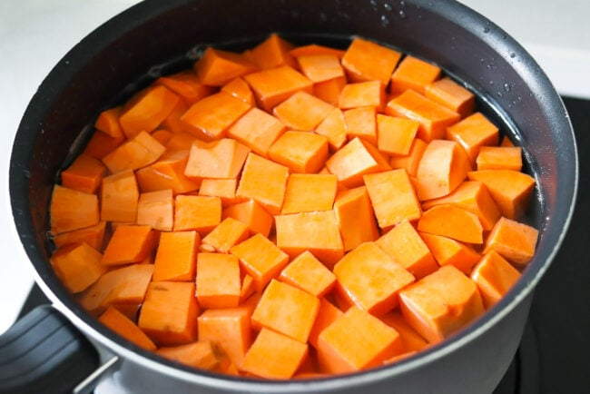 Cubed sweet potatoes in pot with water on stovetop.