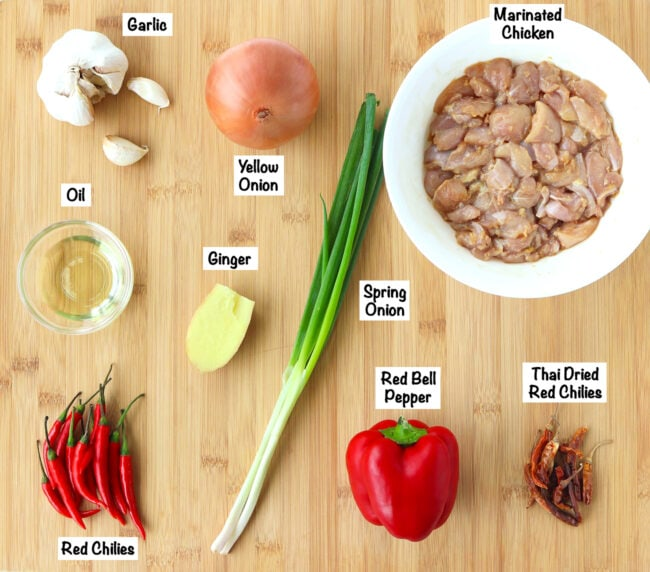 Fresh ingredients for Spicy Pepper Chicken on a wooden board.