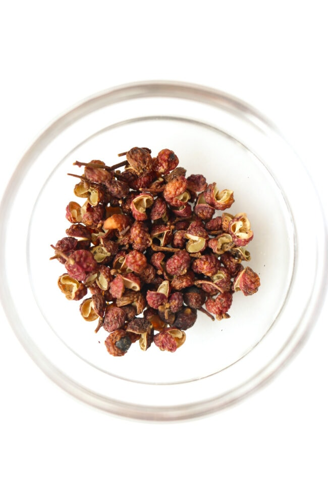 Top view of small bowl with Sichuan red peppercorns.