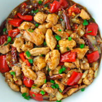 "Top view of a Chinese chicken stir-fry in a bowl. Text overlay "" Spicy Pepper Chicken"" and ""thatspicychick.com""."