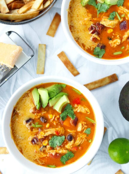 Top view of two bowls with soup topped with diced avocado, coriander, cheese and bowl with tortilla strips behind.