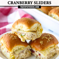 "Front view of three stacked sliders on plate, and sliders in a baking dish in the back. Text overlay, ""Turkey & Chicken Cranberry Sliders"" and ""thatspicychick.com""."