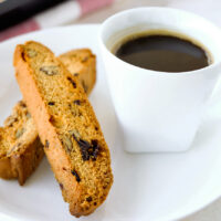Close-up front view of two biscotti and a cup of coffee on a white plate.