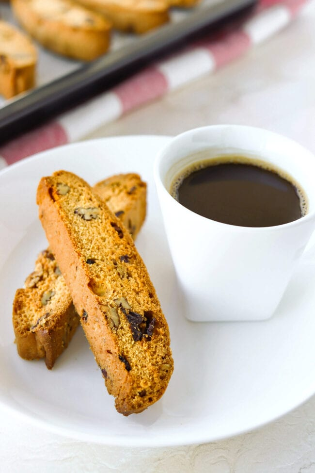 Close-up front view of two biscotti and a cup of coffee on a plate, and baking tray with biscotti in the back.