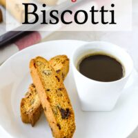 """Two biscotti on plate with cup of coffee, and freshly baked biscotti on tray behind. Text overlay """"Cranberry Pecan Biscotti"""" and """"thatspicychick.com""""."""