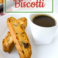 """Close-up of two biscotti on a plate with a cup of coffee, and freshly baked biscotti on tray behind. Text overlay """"Cranberry Pecan Biscotti"""" and """"thatspicychick.com""""."""
