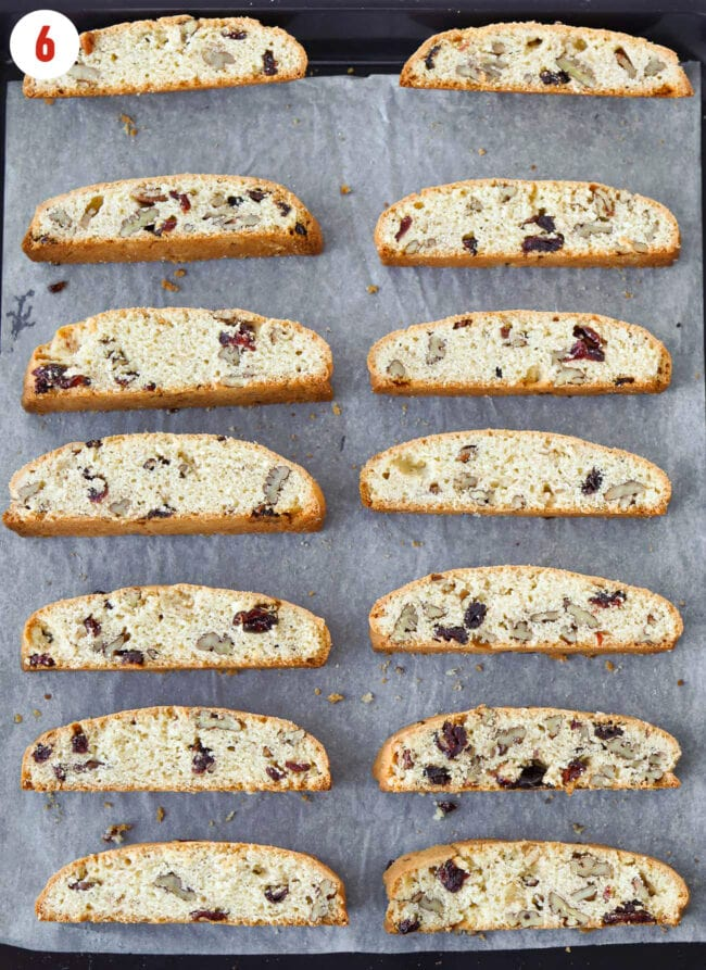 Biscotti pieces cut side down on a parchment paper lined baking tray.
