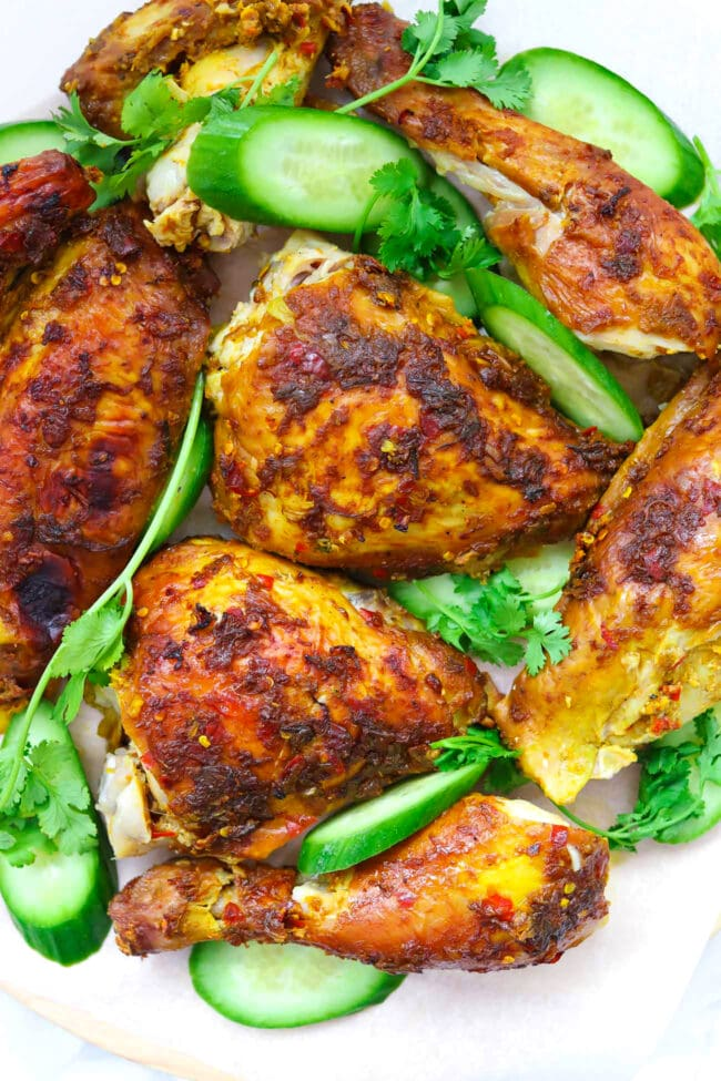Close-up of Spicy Thai Roast Chicken pieces on platter with cucumber slices and coriander sprigs.
