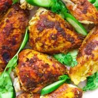 """Close-up of chicken pieces on platter with cucumber slices and coriander sprigs. Text overlay """"Spicy Thai Roast Chicken"""" and """"thatspicychick.com""""."""